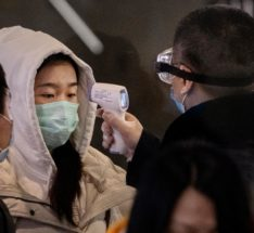 A Chinese passenger is checked for a fever by a health worker in Beijing.