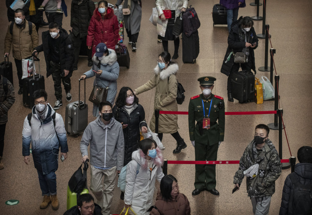Travelers at a railway station in Beijing on Thursday wearing protective masks. China expanded restrictions on travel that will apply to tens of millions of people.Credit...Kevin Frayer/Getty Images (From New York Times 2020/01/23)
